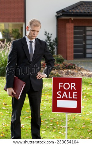 Realtor standing in front of house for sale