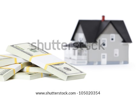 Realty concept - bundles of dollars in front of house architectural model, isolated - stock photo