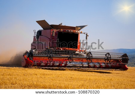 Reaping machine or harvester combine on a wheat field with blue sky and sun behind it