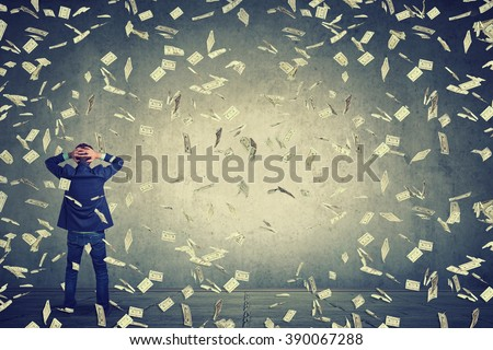 Rear back view of business man standing in front of a wall under money rain dollar banknotes falling down, hands on head wondering what to do next. Full body length of businessman facing the wall - stock photo