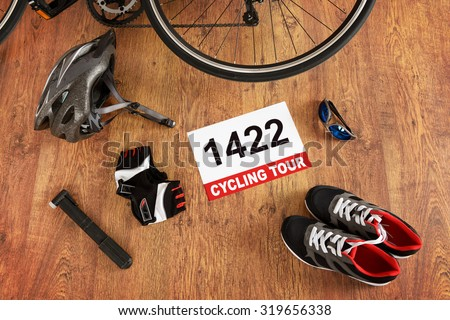 Rear bicycle wheel and other accessories on the wooden floor - stock photo