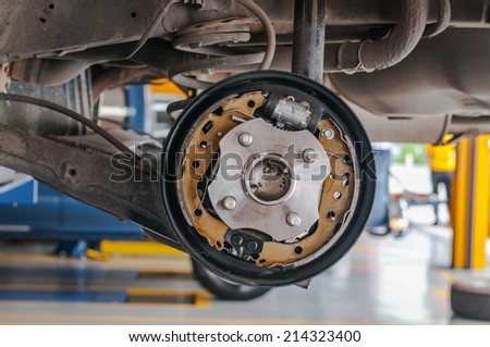 Rear brake disk with caliper partially removed about to be replaced - stock photo