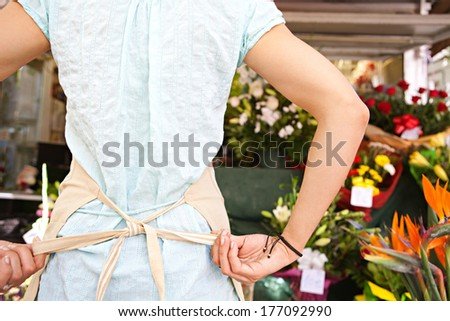 Rear close up of a young florist businesswoman fastening her working apron getting ready for the day work and opening a fresh florist store in a flower market, outdoors business life.