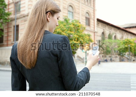 Rear close up portrait view of an attractive smiling young businesswoman using smartphone technology in a classic city, outdoors. (Business, People, Technology) - stock photo