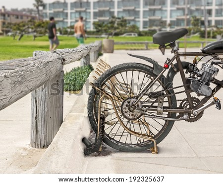 Rear end of dirty motorized bicycle chained to rusty metal bike rack in suburban park. Heavy chain through rear wheel. Motor attached to bike frame. Grass, people, buildings in background.