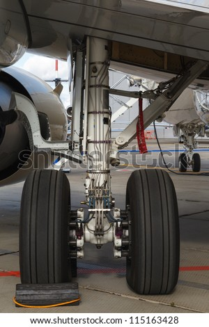 rear landing gear and jet engine passenger plane on the ground - stock photo