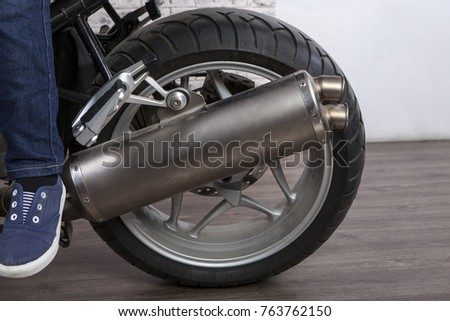 Rear motorcycle wheel with steel exhaust pipe