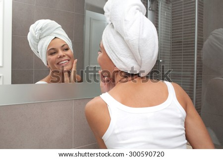 Rear portrait and face reflection of a beautiful joyful young woman applying nourishing cream on her face, looking at herself in a bathroom mirror, with towel on her hair, home interior. Skin care. - stock photo