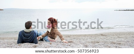 Rear portrait of young tourist couple laying together holding hands on pebble beach winter holiday, having a conversation, contemplating the sea, smiling outdoors. Travel lifestyle, exterior.
