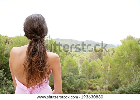 Rear portrait view of a beautiful young woman with bare shoulders relaxing in the forest mountains contemplating nature during a calm summer holiday. Travel and healthy lifestyle and beauty outdoors. - stock photo