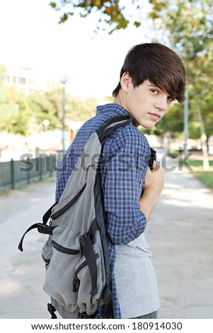 Rear portrait view of a teenager student boy walking on a path at a college campus grounds carrying a backpack and turning to smile at the camera joyfully. Student lifestyle outdoors. - stock photo