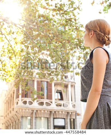Rear portrait view of young tourist woman contemplating sightseeing sunny destination city with direct light flare and classic buildings, exterior. Professional woman in golden aspirational outdoors. - stock photo