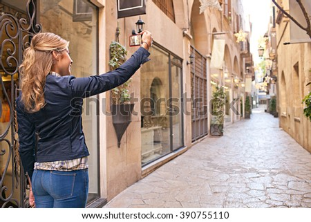 Rear side of caucasian teenager tourist smiling, walking in picturesque city street holding up smart phone taking pictures on holiday, sunny outdoors. Young person using technology, tourist lifestyle. - stock photo