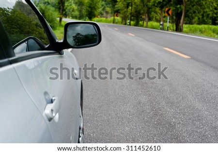 Rear side perspective view of car on road countryside - stock photo