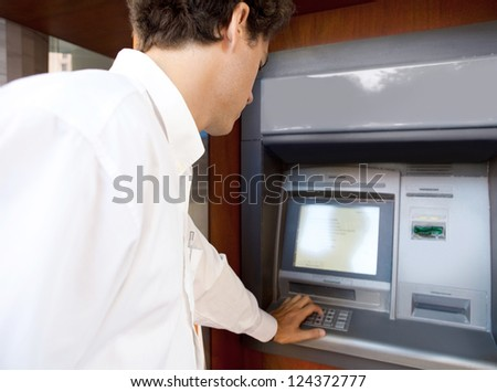 Rear side view of a businessman using an atm machine to withdraw money, outdoors.