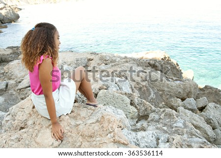 Rear side view of an african american teenager girl sitting on rocks by the ocean, relaxing contemplating the blue sea smiling, outdoors nature. Healthy well being holiday lifestyle, beach exterior.
