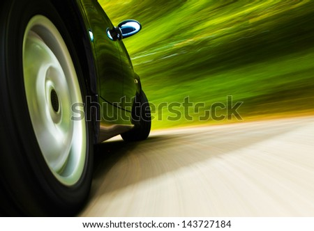 Rear side view of black luxury sedan in turn. - stock photo