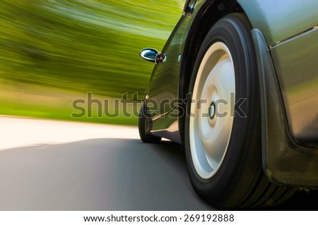 Rear side view of speeding car. - stock photo