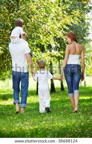 Rear view - a family with two children walks in park - stock photo