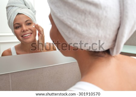 Rear view and face reflection portrait of joyful young woman applying nourishing cream on her face, looking at herself in a bathroom mirror, with towel wrapping her hair, home interior. Skin care. - stock photo