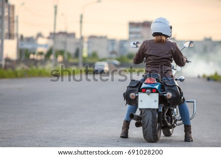Rear view at young woman a motorcyclist ready to start riding on motorcycle on asphalt road, copy space