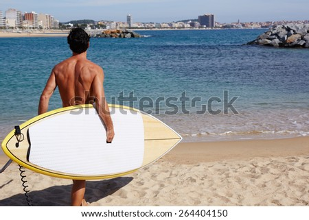 Rear view attractive man with sexy body going to the sea holding big copy space surfing board, handsome man walking on shoreline at beautiful sunny day, professional surf rider began his surf session - stock photo