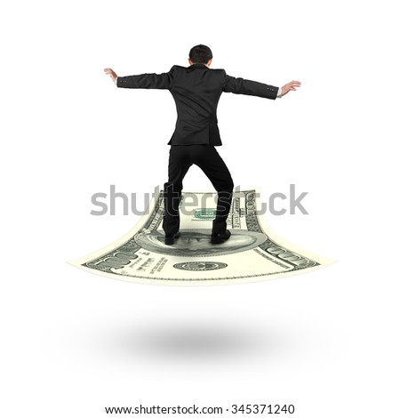 Rear view businessman balancing on money flying carpet, isolated on white background. - stock photo