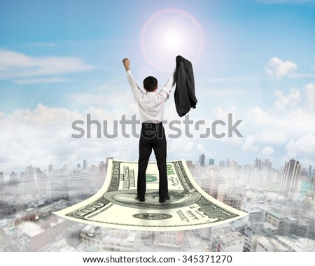 Rear view businessman cheering and standing on money flying carpet, with sunny sky cityscape background. - stock photo