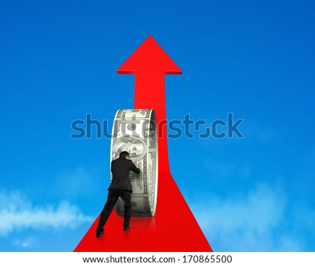 Rear view businessman pushing money circle on growing red arrow in blue sky background - stock photo