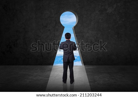 rear view businessman standing cross one's arm front of keyhole on old grunge black wall against bright blue sky background - stock photo