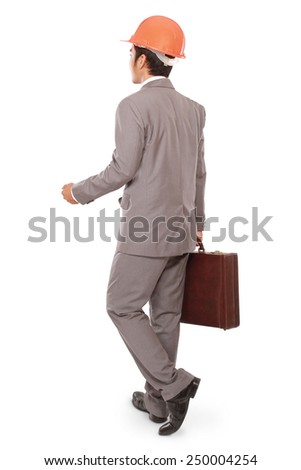 rear view businessman walking with builders helmet and carrying a suitcase isolated on white background - stock photo