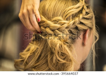 rear view closeup of a hairdresser braiding her clients hair in trendy weave plait while sitting in hairdressing salon