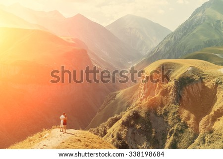 Rear view, couple hikers looking into the distance, is standing on the top of mountain. Background is mountains, valley and cloudy sky. - stock photo