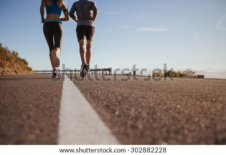 Rear view cropped shot of two young people running together on road. Man and woman on morning run on summer day. Low angle shot of couple jogging outdoors. - stock photo