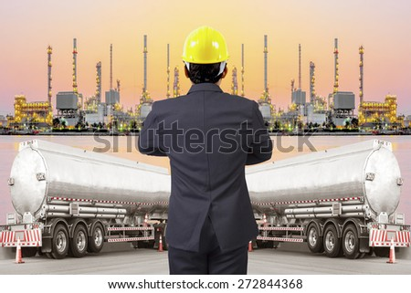 rear view engineer standing cross one's arm chest working with tanker truck for transport fuel to petrochemical oil refinery in sunrise - stock photo