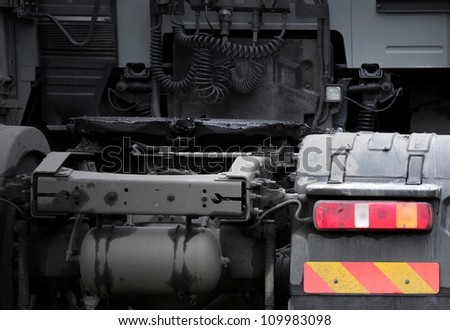 Rear view fragment of truck tractor with bright taillight and striped sign - stock photo