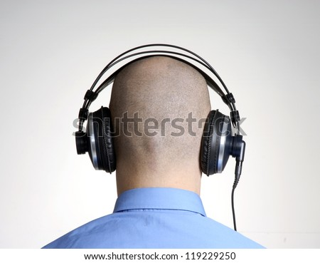 Rear view from an adult bald head man using headphones. - stock photo
