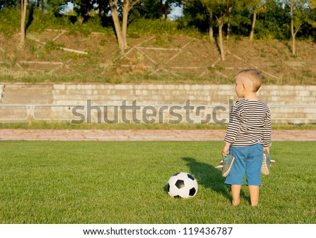 Rear view image of a small barefoot boy standing with his shoes in his hands alongside a soccer ball on green grass with copyspace