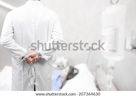 rear view image of doctors with stethoscope in a hospital pose arms crossed behind back looking at nurse pushing stretcher gurney bed in labour room of hospital corridor with female patient pregnant - stock photo