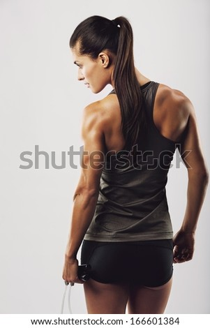 Rear view image of female bodybuilder holding skipping rope looking away. Young fitness woman with muscular body posing on grey background - stock photo