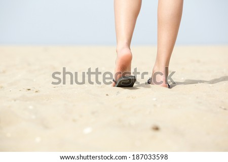 Rear view low angle woman walking away at beach in sandals - stock photo
