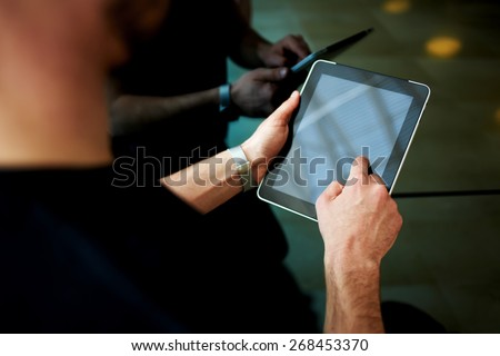 Rear view male person using digital tablet, business man or freelancer working on touch pad in elevator, businessman executive using wireless devices in modern office, young successful browsing on pad - stock photo