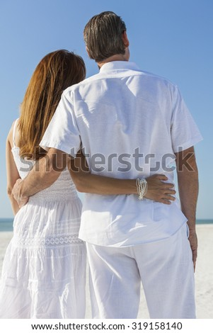 Rear view man and woman romantic couple embracing on a deserted tropical beach with bright clear blue sky