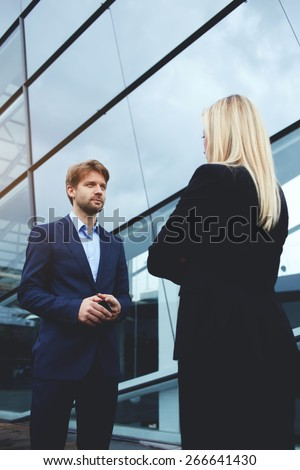 Rear view managing businesswoman with crossed arms standing opposite smiling employee outside office, business colleagues having conversation or discussion, businessman with cellphone talking to boss - stock photo