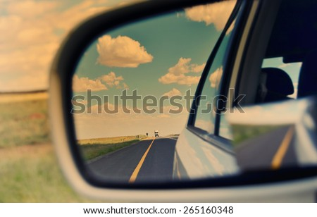 Rear view mirror and long road through arid landscape - stock photo