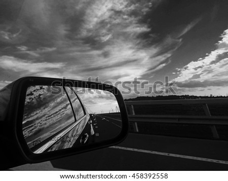 Rear view mirror reflecting road and sky - stock photo