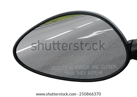 Rear view mirror with warning text objects in mirror are closer than they appear, isolated, reflecting road, left side lateral, macro closeup, tarmac asphalt reflection, white lines, arrows marking - stock photo