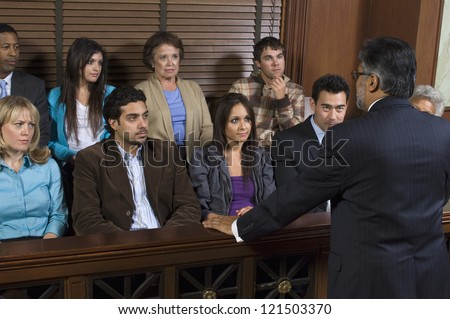 Rear view of a advocate communicating with the jurors in the court house - stock photo