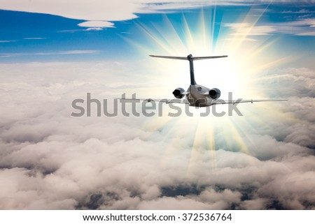 Rear view of a airplane that is flying high above the clouds - stock photo