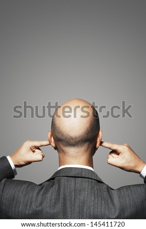Rear view of a bald businessman with fingers in ears against gray background